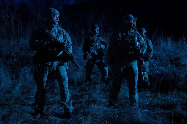 Leger speciale operaties tactische groep, militaire saboteurs team gewapende jagers staan 's nachts in grasachtig gebied, verbergen gezichten achter maskers, bewegen zich stil in het donker, patrouilleren in de buurt