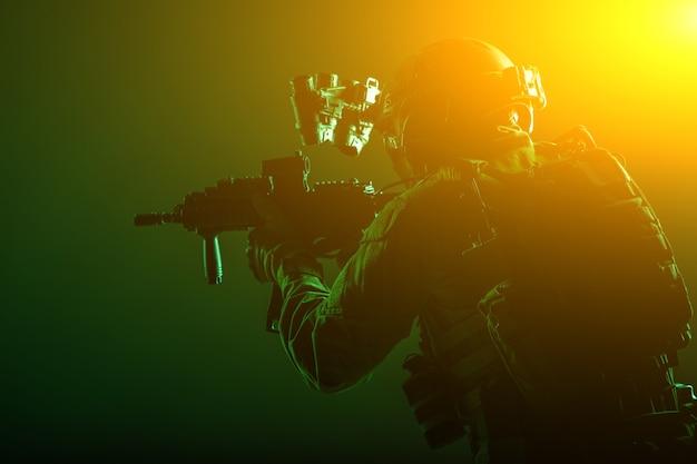 Legersoldaat, strijder tegen terroristische squadron, huursoldaat van militaire compagnie in munitie en kogelvrije vesten, helm met nachtzichtapparaat, gericht met dienstgeweer met korte loop, low key, studio-opname
