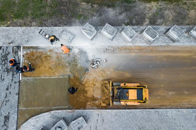 Leggen van bestratingplaten op het voorbereide betonoppervlak. reparatie van het voetpad in de stad. stedelijk gemeentelijk werk