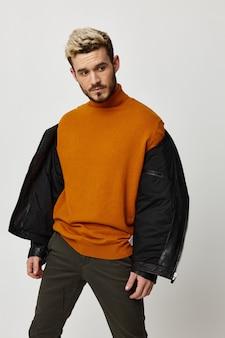 Legging in een oranje sweater met een losgeknoopt jasje op de schouders