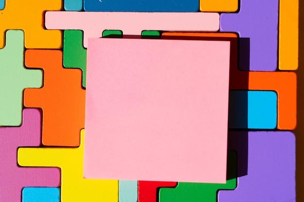 Legpuzzels, werelddag voor autisme, kopieer ruimte op roze notitie