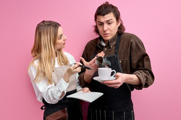 Leidende vrouwelijke ober dient klacht in tegen een onervaren mannelijke ober, praat tijdens het werk, legt uit hoe u bestellingen van klanten opneemt.