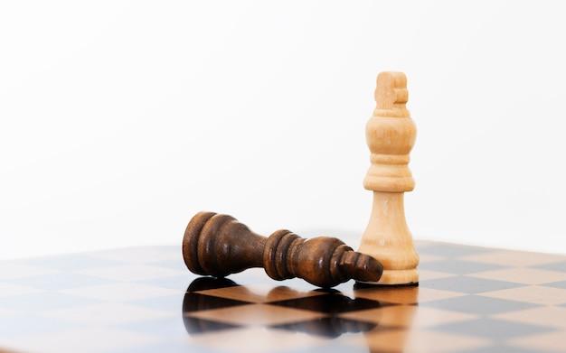 Leider en concurrentie. white chess king onder liggen zwarte pionnen op schaakbord