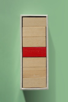 Leiderschap en influencer concept. een rode en veel houten blokken die in een doos stapelen. individualiteit en uniciteit. dominante leider of baas.