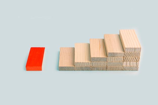 Leiderschap en influencer concept. houten blokken stapelen als opstap en volgen een rood op blauwe achtergrond. individualiteit en uniciteit. sociale afstand. dominante leider.