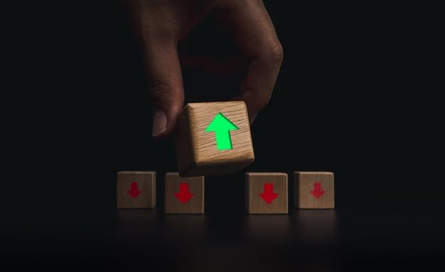 Leiderschap, ontwikkeling en denk verschillende concepten. hand die het houten kubusblok met groene, pijl-omhoog voor de rode pijl-omlaag blokken op een donkere achtergrond zet.