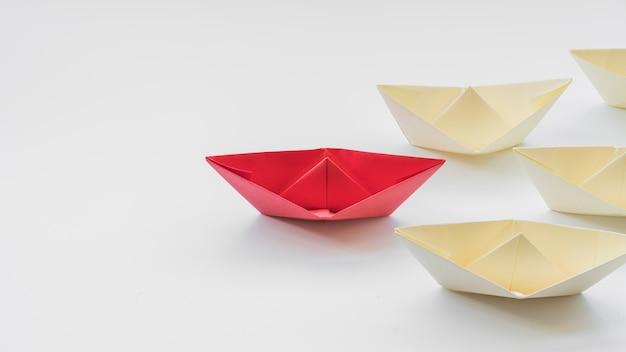 Leiderspapierschip gevolgd door witte boten