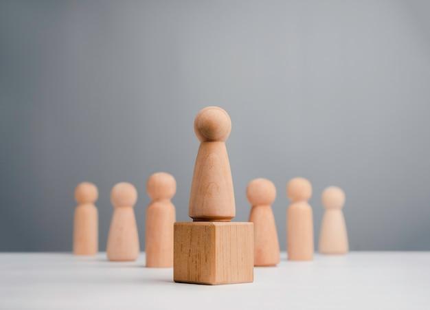 Leidervrouw, beïnvloeder, vrouwen in leiderschapspositieconcept. houten figuur, sterke vrouw die op de doos staat en team, minimalistische stijl.