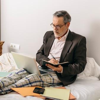 Leidinggevende van middelbare leeftijd die aantekeningen maakt tijdens een werkvideoconferentie