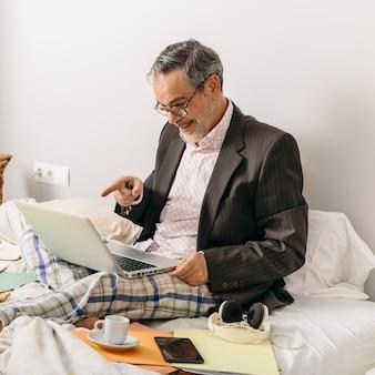 Leidinggevende van middelbare leeftijd die deelneemt aan een zakelijke bijeenkomst via videoconferentie vanuit het kantoor op zijn thuisbed