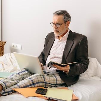 Leidinggevende van middelbare leeftijd die een zakelijke bijeenkomst bijwoont via videoconferentie vanuit het kantoor op zijn thuisbed