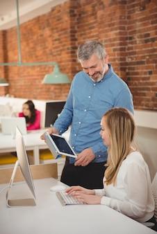 Leidinggevenden bespreken over digitale tablet aan balie