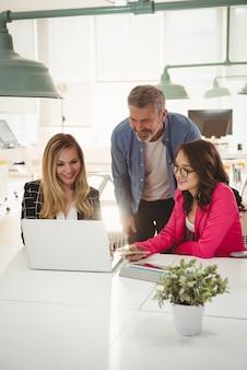 Leidinggevenden die over laptop bij bureau bespreken