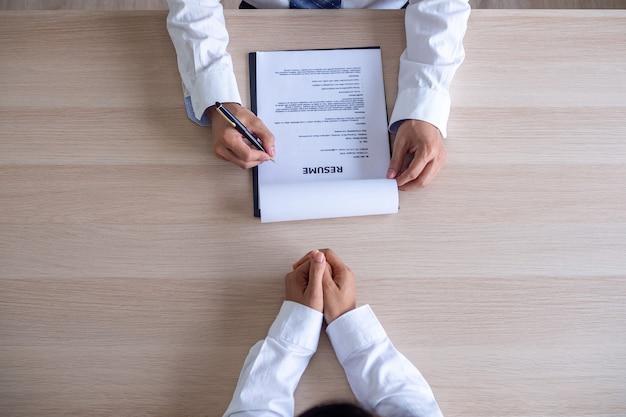 Leidinggevenden lezen cv's tijdens sollicitatiegesprekken en zakenmensen vullen sollicitatieformulieren in, beantwoorden vragen en leggen eerdere werkervaring uit. inhuur concept