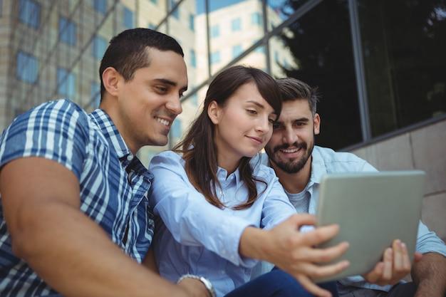 Leidinggevenden met behulp van digitale tablet buiten het kantoorgebouw