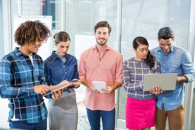 Leidinggevenden met behulp van laptop, digitale tablet en mobiele telefoon