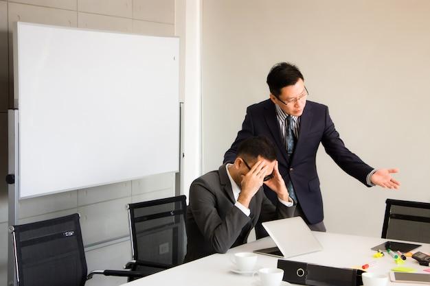 Leidinggevenden verduidelijken taakfouten aan de supervisor. hij had een ernstig gezicht en had een donker hoofd in zijn hoofd als hoofdpijn in de vergaderruimte.