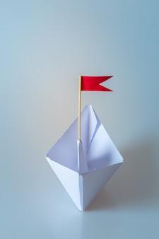 Leidingsconcept die document schip met rode vlag op blauw gebruiken