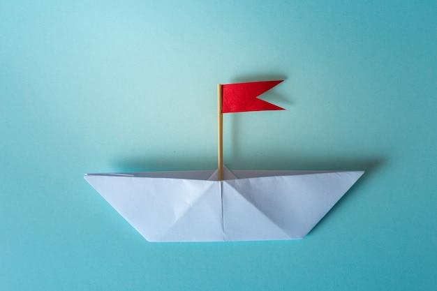 Leidingsconcept die document schip met rode vlag op blauwe achtergrond gebruiken