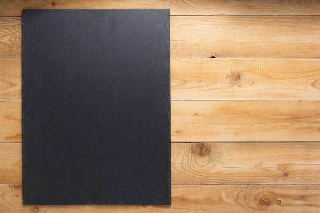 Leisteen bord op houten plank, achtergrond textuur oppervlak