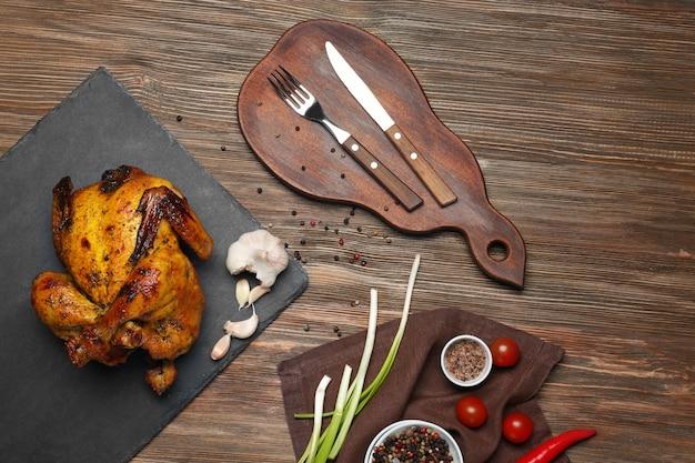 Leisteen plaat met geroosterd bier kan kip op houten tafel