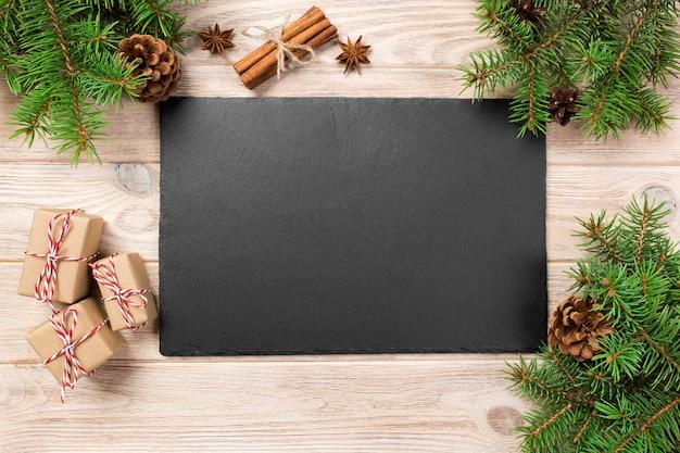 Leisteen schotel op houten tafel met kerstdecoratie. zwarte leisteen op houten oppervlak.
