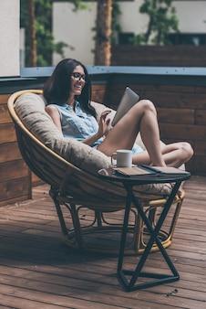 Lekker buiten genieten. mooie jonge vrouw die aan haar digitale tablet werkt en glimlacht terwijl ze in een grote comfortabele stoel op haar buitenterras zit