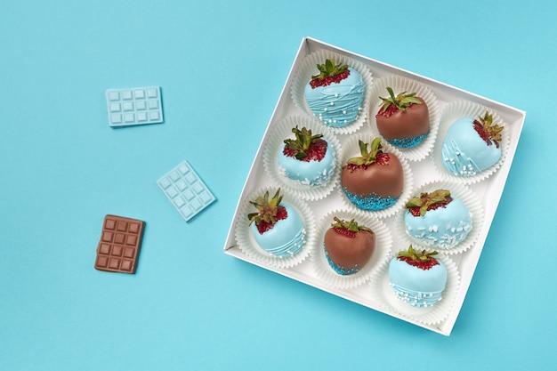 Lekker dessert in de vorm van rijpe aardbeien in chocolade op een turkooizen achtergrond