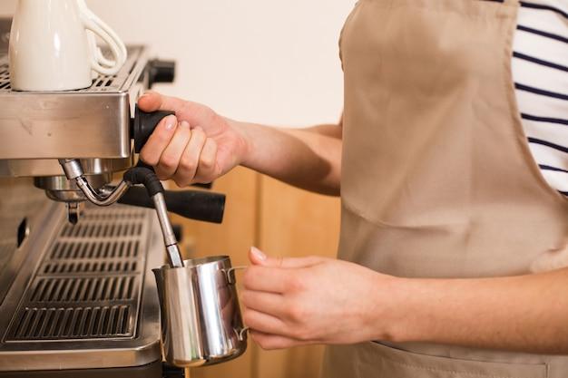 Lekker drankje. close-up van koffie die wordt bereid door een leuke, aangename vrouw tijdens het werken in het café