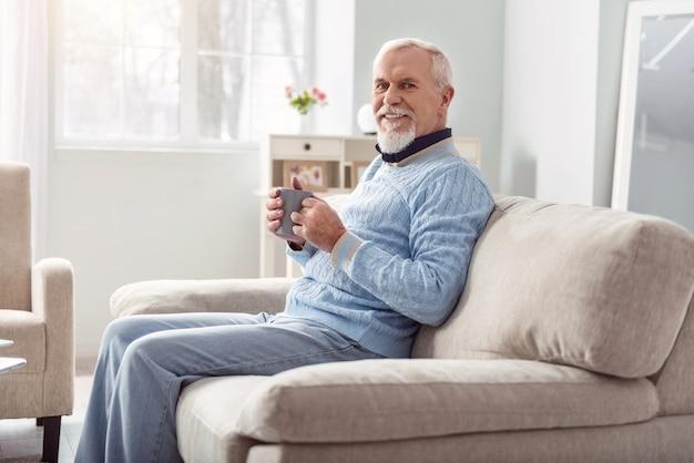 Lekker drankje. vrolijke senior man zittend op de bank in de woonkamer en lacht tijdens het drinken van koffie