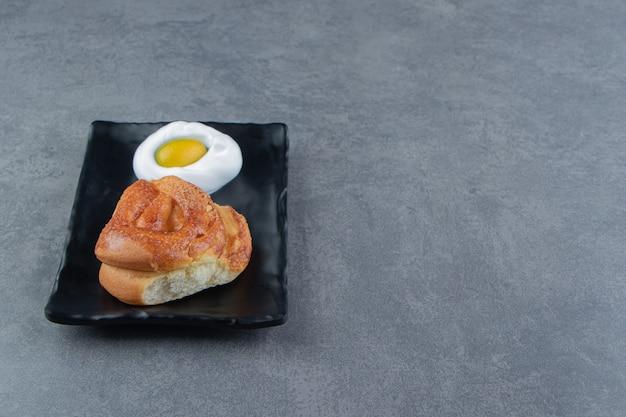 Lekker eigengemaakt vers broodje op zwarte plaat.