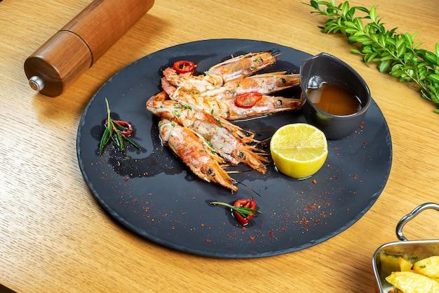 Lekker en luxe eten. gegrilde langoustines op donkere stenen plaat met saus en citroen. restaurant food styling. heerlijke zeevruchten op houten