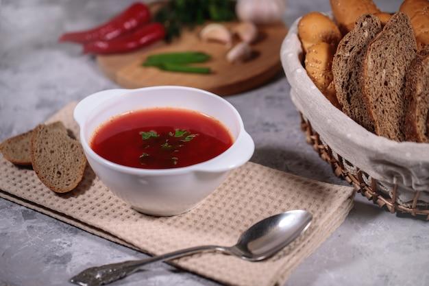 Lekker en stevig diner. een bord met borsch op de tafel, naast het bord is peterselie, dille, groene uien, knoflook, chili peper en een mand met brood.