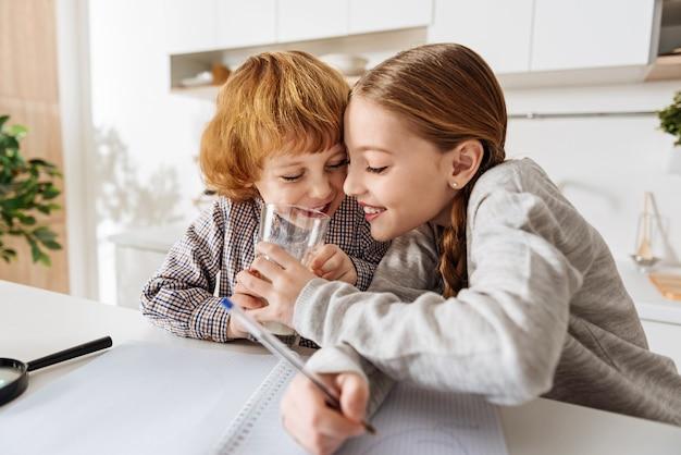 Lekker en voedzaam. mooi humoristisch jong meisje plaagt haar broertje door te proberen zijn melk te drinken terwijl ze aan haar thuistoewijzing werkt