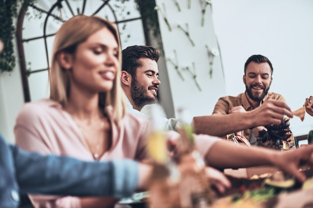 Lekker eten en goede vrienden. groep jongeren in vrijetijdskleding die eet en glimlacht