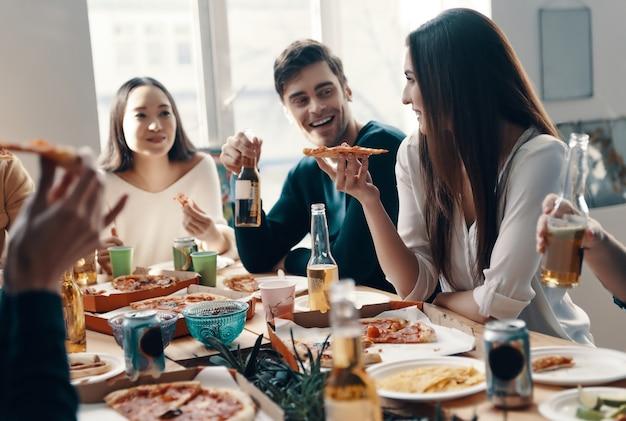 Lekker eten en goede vrienden. groep jongeren in vrijetijdskleding die pizza eet en glimlacht terwijl ze binnen een etentje hebben