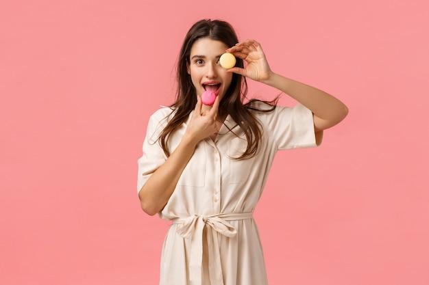 Lekker eten, geluk en snoep concept. gelukkig vrij kaukasisch brunette in kleding, die macaron op oog houdt en dessert met tevreden opgewekte glimlach eet, die roze muur bevindt zich