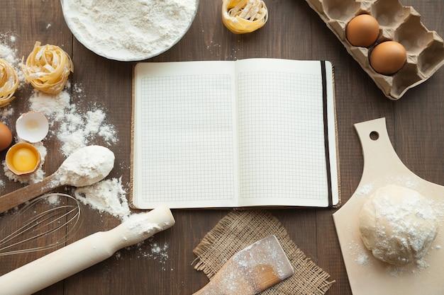 Lekker eten koken en recept opschrijven in open duidelijke notitie. met ingrediënten als eieren, bloem, pasta en deeg.