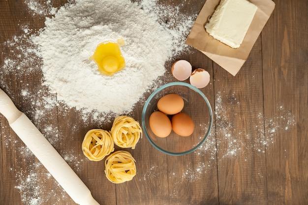 Lekker eten koken. met ingrediënten als boter, eieren, bloem, pasta. uitzicht van boven