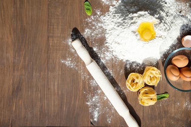 Lekker eten koken. met ingrediënten als eieren, bloem, pasta, muntblaadjes. uitzicht van boven.