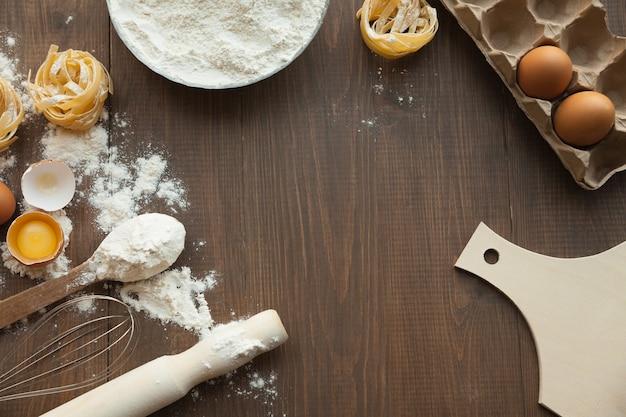 Lekker eten koken met ingrediënten zoals eieren, meel, pasta en deeg. boven het hoofd.