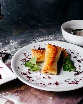 Lekker gebak lekker vlees gevuld met groene bladeren en sumax in witte plaat op het lichte oppervlak