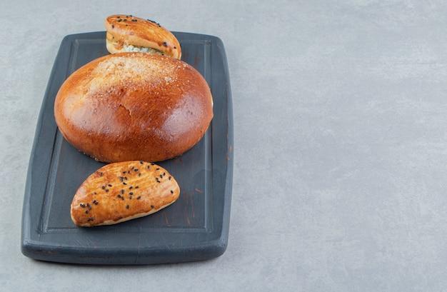 Lekker gebak met kaas en broodje op zwart bord.