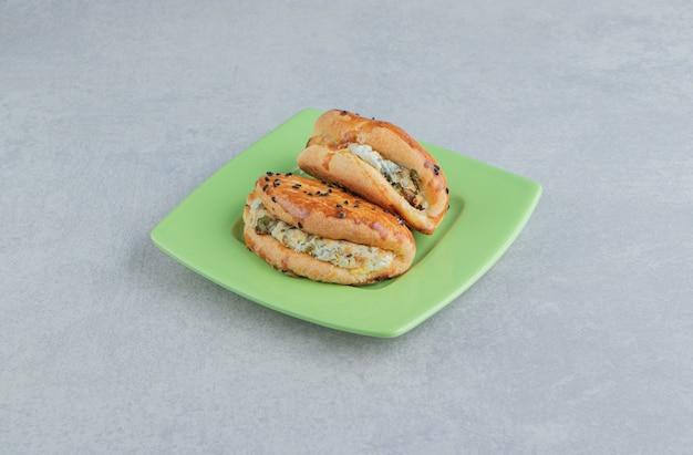 Lekker gebak met kaas op groene plaat.