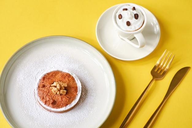 Lekker gebak taarten met noten en een kopje koffie op een gele muur.