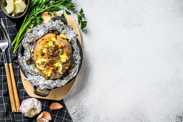 Lekker gebakken aardappel gegarneerd met cheddarkaas en bieslook. bovenaanzicht. kopieer ruimte
