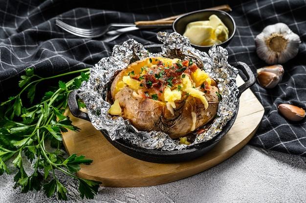 Lekker gebakken aardappel gegarneerd met cheddarkaas en bieslook. witte achtergrond. bovenaanzicht