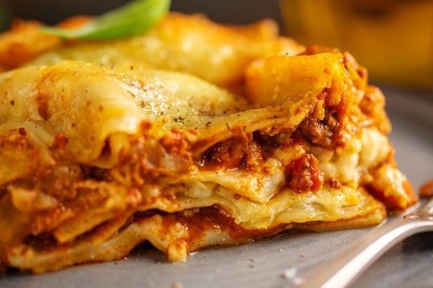 Lekker gebakken bereide klassieke italiaanse lasagne in braadpan op lichte achtergrond. detailopname