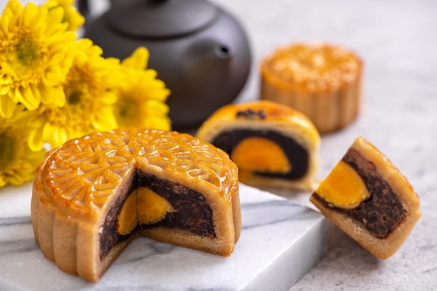 Lekker gebakken eidooier gebak maan cake voor mid-autumn festival op heldere cement tafel achtergrond. chinees traditioneel voedselconcept, close-up, kopieer ruimte.