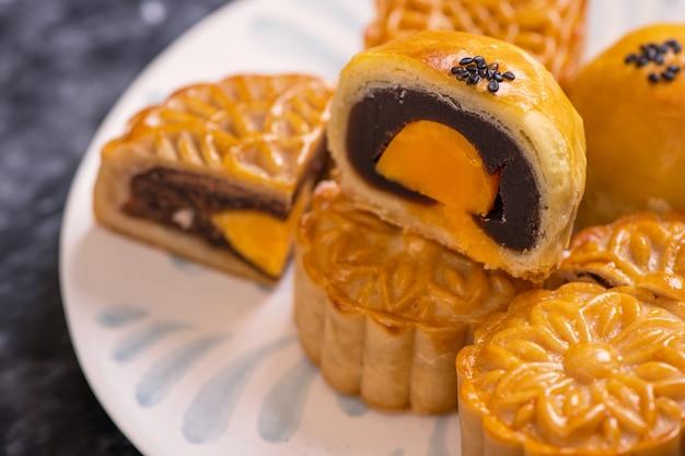 Lekker gebakken eidooiergebak maancake voor mid-autumn festival op zwarte leisteen donkere achtergrond